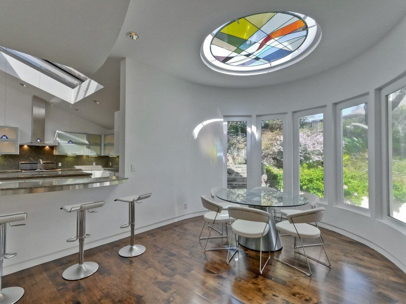 a-small-dining-area-has-a-stained-glass-window-as-a-skylight